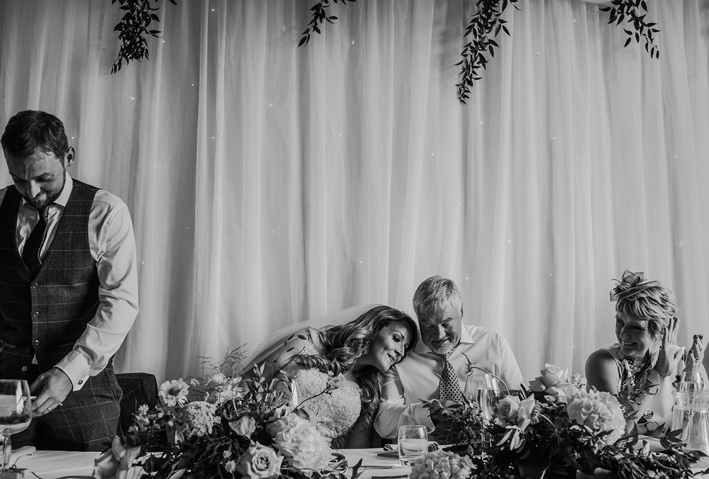 bw photo of bride resting her head on her dad's shoulders
