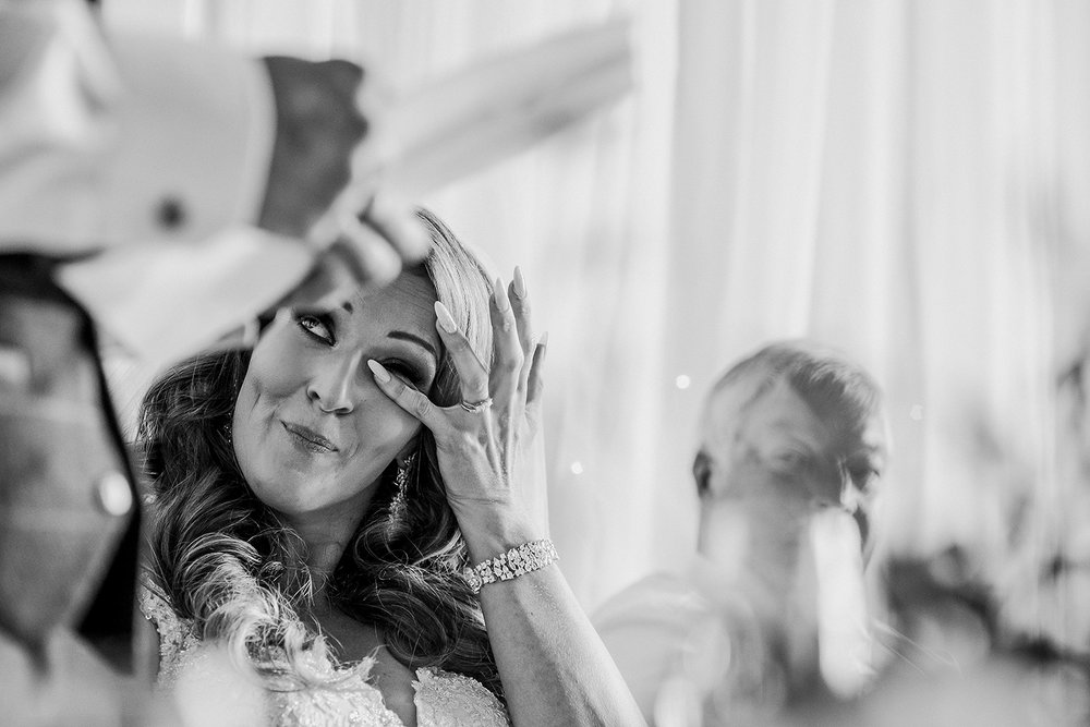 bw photo of the bride wiping a tear during the groom speech