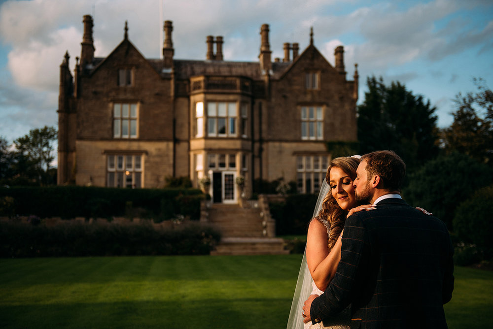 bride and groom portrait with falcon manor in the background