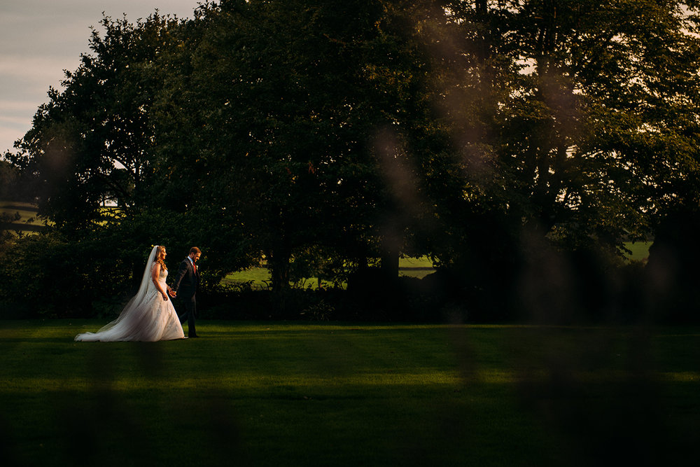 bride and groom walking along a beam of light in the gardens
