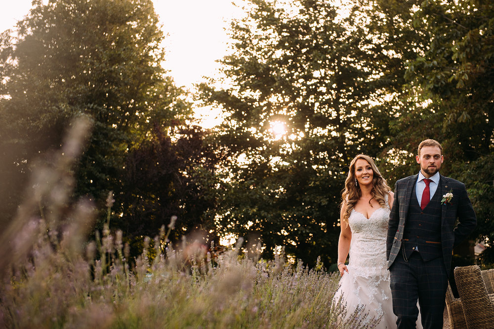 bride and groom walk past lavender at the front of falcon manor