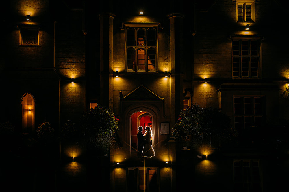 night time couple portrait at the front of the manor with a reflection