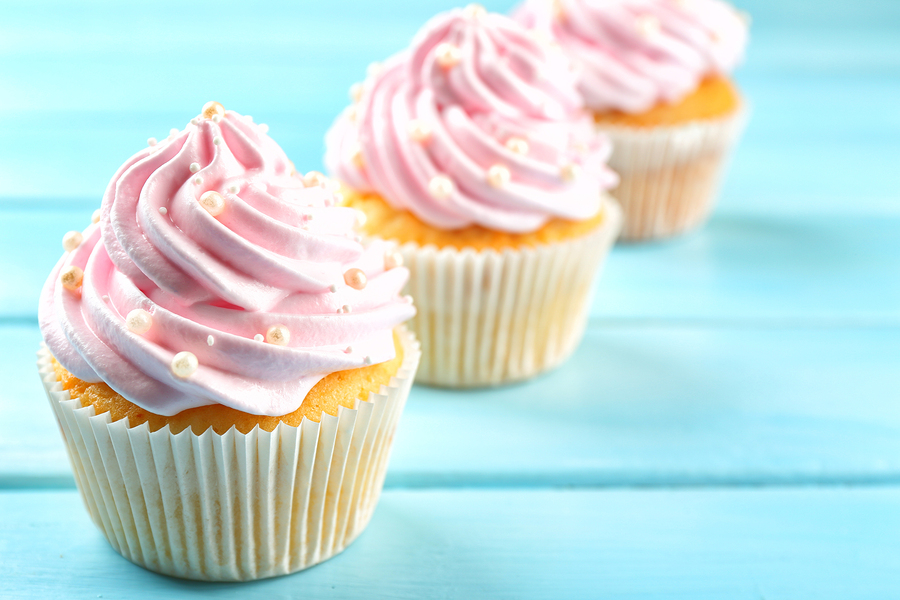 bigstock-Pink-cupcakes-on-wooden-backgr-116469635.jpg
