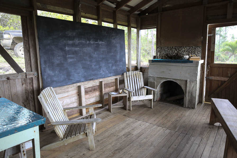 The cabin is equipped with kitchen and dining room, screened porch with wood fireplace for lectures and common meeting space.