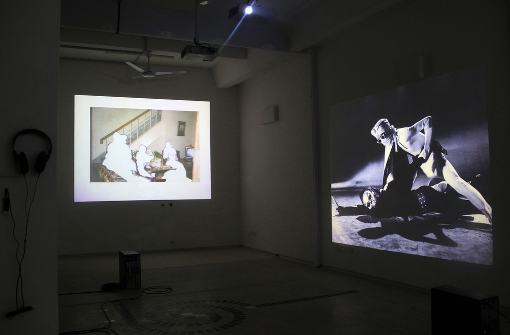 Exhibition view, to the left is Rabbya Naseer and Hurmat Ul Ain,  Reenactment  (2012) and at right, Mehreen Murtaza,  This Film Should Be Played Loud   ( 2012). Photograph by Sadia Shirazi.