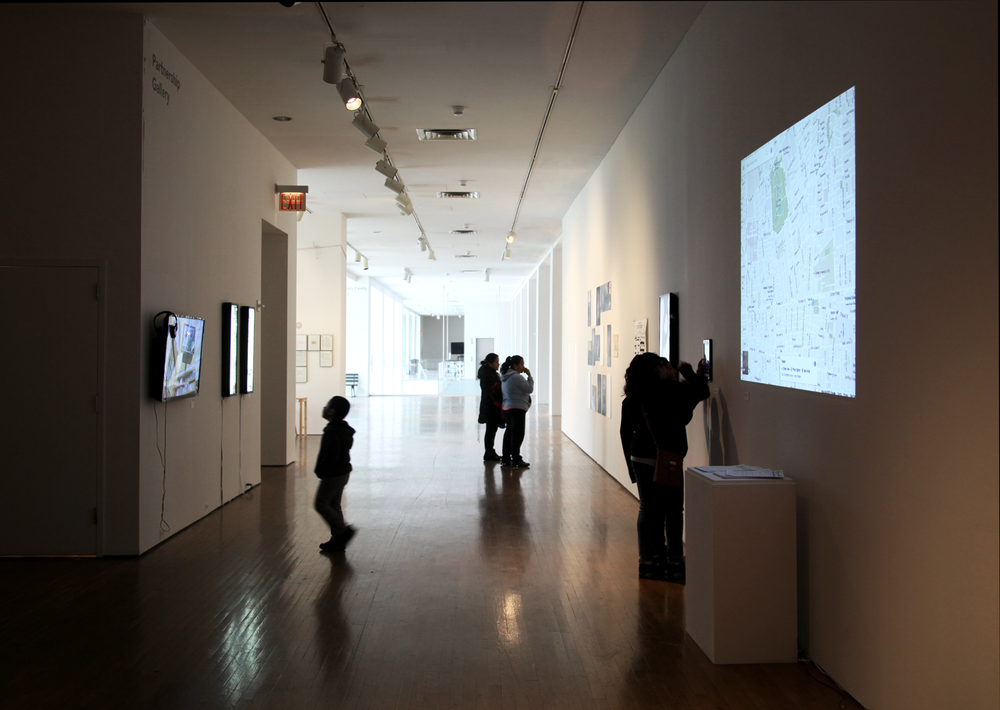 Exhibition view, with Anushya Badrinath's video  Kuwait, Egypt, India  (2013-16) to the left alongside Chitra Ganesh and Mariam Ghani's lightboxes  The Index of Democracy Is The Interval Between Inquiry and Info  (2013) and  Reasonable Articulable Suspicion  (2013), photograph by Sadia Shirazi.