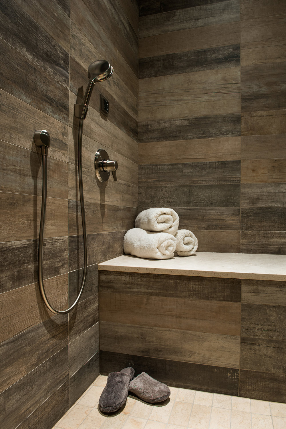I could easily relax in this steam room with wrap around, barn wood style tile.