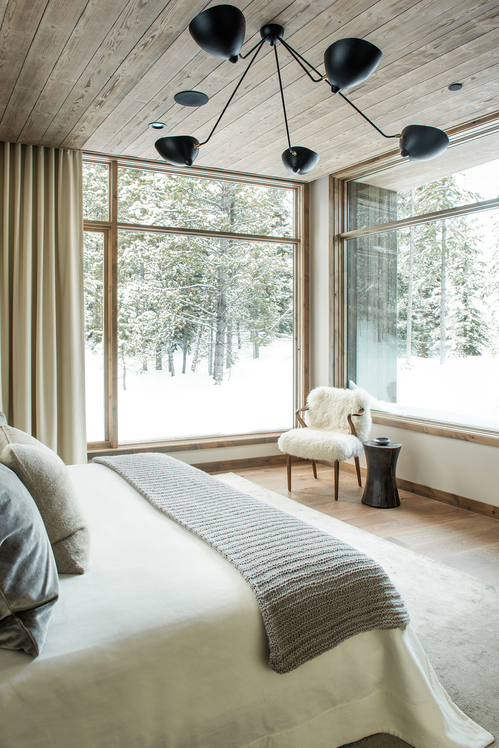 Talk about a room with a view.  The windows are what make this master suite so architecturally stunning.  The furnishings add lovely textures that add to the splendar of the room.