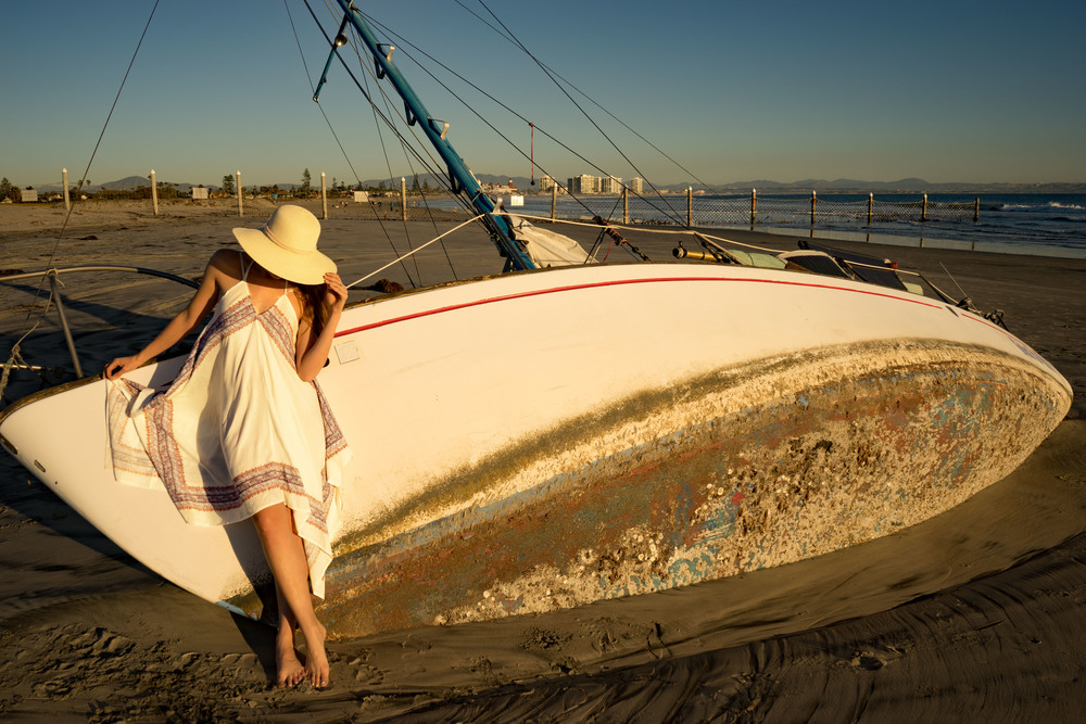 Water Wanderer leaning against a sail boat on Coronado beach, wearing O'Neill dress.
