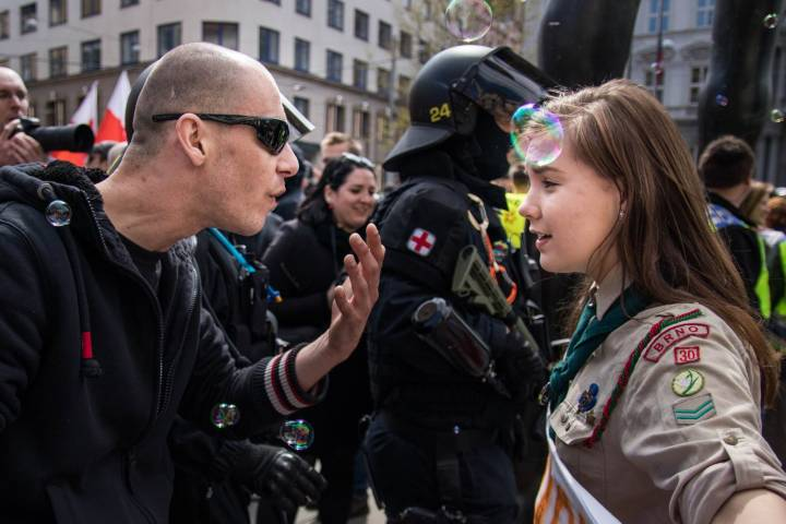 A Girl Scout, only identified as Lucie, stand her ground against a Neo-Nazi  at the May Day rally in Brno. Photo: Vladimir Cicmanic
