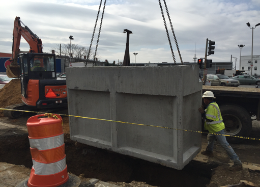 Lowering standard double inlet I-48 into trench just south of Dix St.