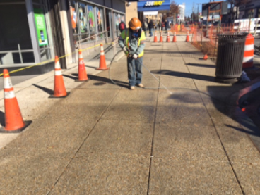 Performing final cleaning of new exposed aggregate sidewalk, w. side Minn Ave b/t Dix St. & Benning Rd.