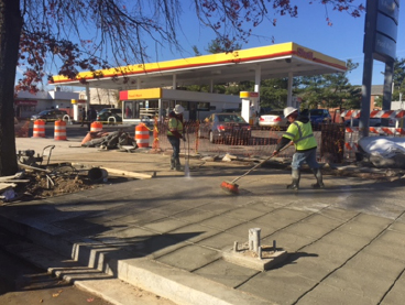 Washing/scrubbing cement top layer off sidewalk to expose aggregate finish, w. side IFO Shell Station