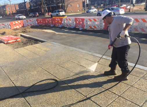 Power-washing/scrubbing sidewalk to expose aggregate finish, w. side b/t Ames St. & Bridge