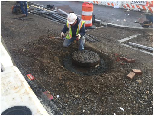 Adjusting existing utility manhole frame & cover to new sidewalk grade, w. side b/t Clay Pl. & Dix St.