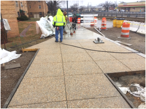 Power-washing new sidewalk to expose aggregate stone finish @ Ridge Rd., e. of Minn. Ave.