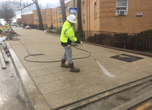 Power-washing new sidewalk to expose aggregate stone finish, w. side Minn. Ave. b/t A St. & Ridge Rd.