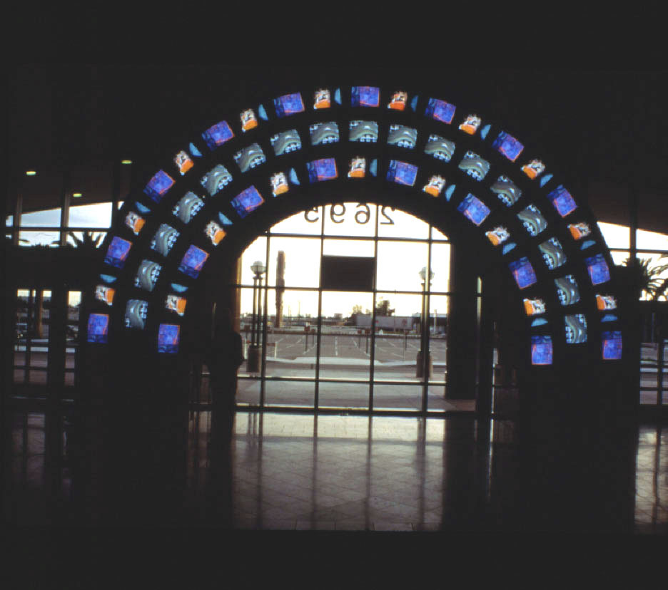 One of a only a few public commissions for Nam June Paik,  Video Arch  responds to the architecture of the facility in its use of the arch.  Each of the two sides of the arch are filled with 53 monitors, displaying an ever-changing range of imagery derived from Paik's own inventory as well an additional inventory culled from a massive responsive of donated images from Anaheim residents.  Awarded Best Public Art of 1996 by Architectural League of Orange County.