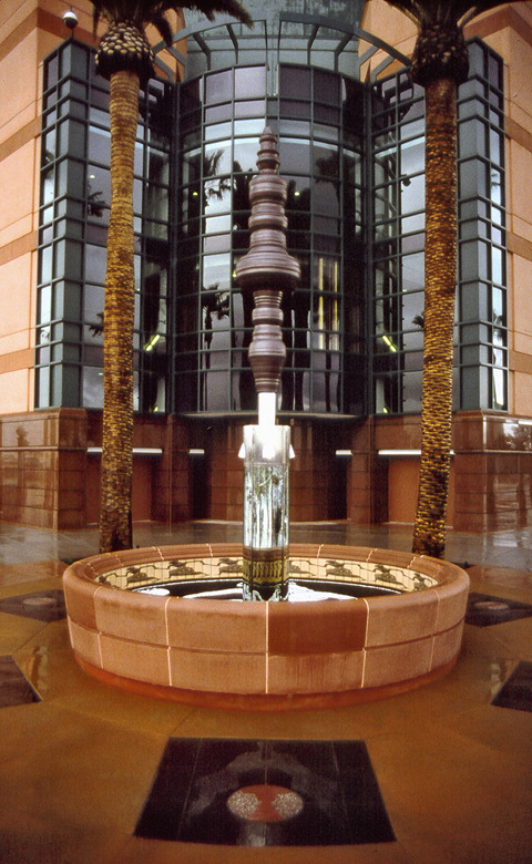 "Situated in the most prominent corner on the outside of the Honda Center,  Anamorph  by the team of Michael Davis, Ann Preston and Richard Turner, invites viewers into the spectacle of seeing.  Anatomically distorted figures in the sculpture's basin are restored to accuracy through the viewer's engaging the reflections in the mirrored column in the sculpture's center.  The three-dimensional ""rorschach"" atop the mirror column emphasizes the role of the visual perspective in interpreting the spectacles that occur within the arena.   Anamorph    was awarded Best Public Art by the Architecture Foundation of Orange County in 1996.     Link"