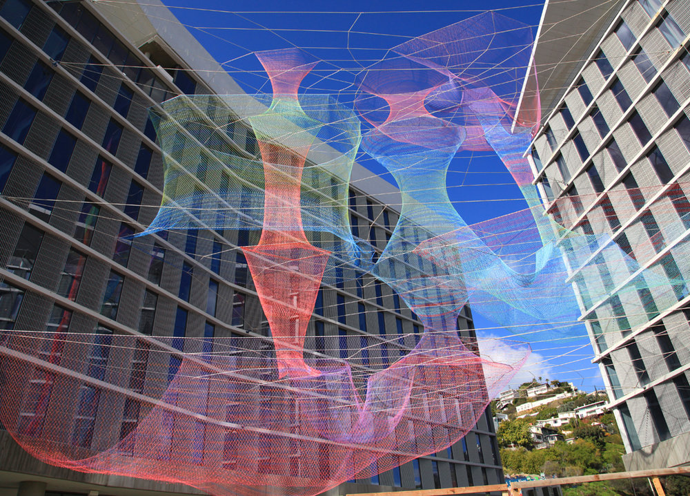 Dream Catcher offers a unique response to the site's formal parameters. Situated between the two ten-story buildings Echelman used attachment points on four different levels allowing for the complexity of the sculpture. On the left of this image one can see an attachment point into the eighth floor concrete slab. The white cables provide the sculpture's support on all four levels and the colored sculptural forms are suspended from and within them. The color palette of Dream Catrcher changes drastically even in daylight depending upon the degree of cloud cover and the position of the sun.  Photo courtesy of: Nicole Wang/SOM Engineering, Courtesy Echelman Studio