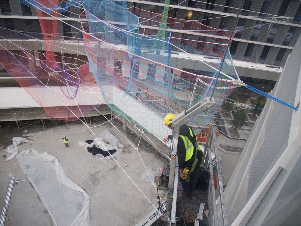 The sculpture is being installed in multiple stages and here the soft and unorganized masses of net are about to be pulled into their final shape. The attachment point on the right of the image shows the structural net and its blue cable connector being tightened into the attachment hardware embedded into the concrete floor.