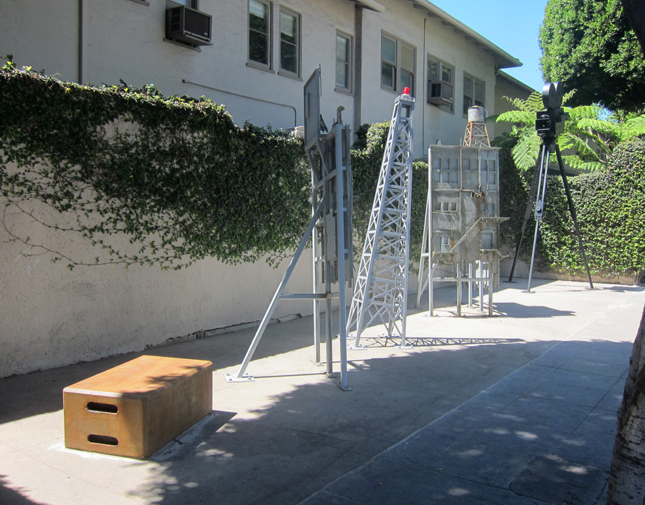 "The sculptures descend from the tallest on the west end of the plaza (the camera) to the shortest on the east end (the apple crate). The sightline from the tallest (the camera at 14"") to the shortest directs visitors' attention to the three viewing portals set into the garage door. The apple crate is a typical utilitarian object used by grips to store cables and other materials as well as provide easy seating and/or height assistance. The derrick with the red light, like the two flats that flank it, is placed at an angle, creating a sense of dislocation and dynamism that is reminiscent of the sense of wonder that surrounds the production of movies."