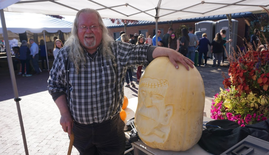 Tim Pate stands by his large carved pumpkin at the 2018 West Coast Giant Pumpkin Regatta in Tualatin, Oregon.