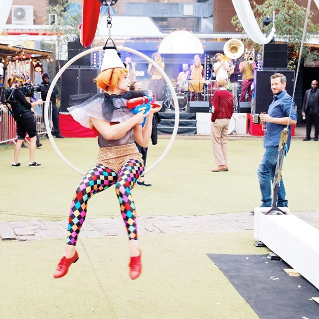 Acrobatic clown spraying water over baffled punter. — #wildandserene #lagunitasbeercircus #circus #clown #acro #playfull @bearded_kitten #london #beerfestival #eyecontact #arlequina #early #waterpistol #funtimes #eventphotography #immersive #festival #festivalfashion #performer #early #warmup #loosenup