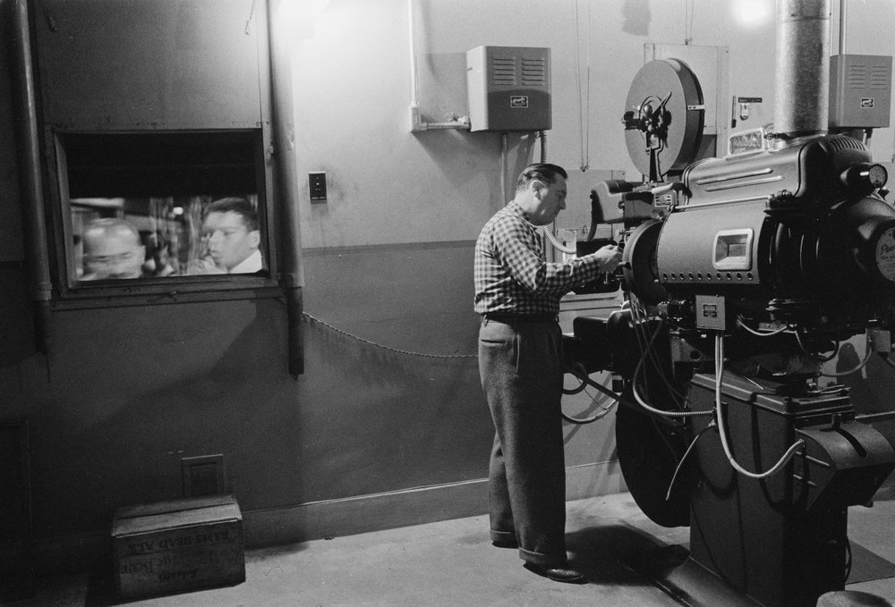 Man_working_with_a_projector_in_a_movie_theater_1958.jpg