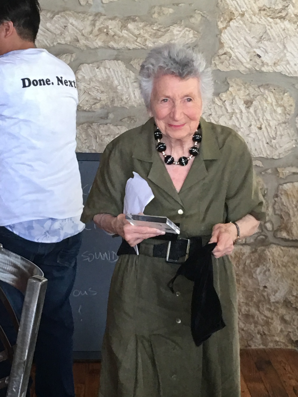 Adam Rocha in the background wearing our official DONE. NEXT! T-shirt, moments after giving Marcia the Lifetime Achievement Award.