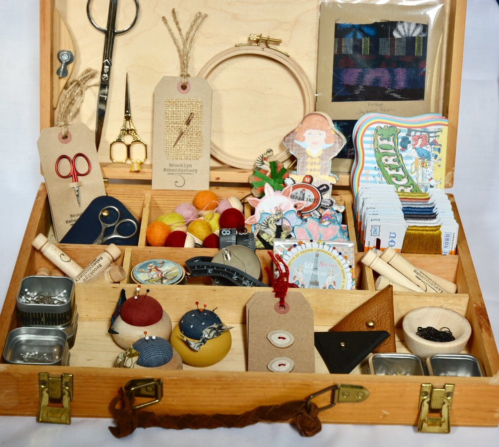 TOOLS and NOTIONS  The case of notions is always a treasure trove! Front Row (l to r) Glass Head Pins -- $8.50, Turned Wood Pin Cushions -- $19.50, Antler Buttons -- $7, Leather Envelope of Stitch Markers -- $23, Tin of Stitch Markers -- $7; Second Row (l to r) Embroidery Needles in Wooden Case -- $8.50, Triangle Head Pins -- $12, Stainless Winding Tape Measure -- $22, Rosette of Glass Head Pins -- $10.75, Knitter's Darning Needles in Wooden Case -- $11; Third Row (l to r) Tiny Red Scissors -- $18, Leather Scissors Case with Scissors -- $29, Wool Pin Cushion Rings -- $12, Thread Winders -- 3/$5, Embroidery Floss -- $3/10, Needle Books -- $21.50; Back Row in Lid of Case (l to r) Flat-Handled Scissors --$28, Eiffel Scissors --$15, Thorn Needle -- $12, Wood Embroidery Hoop -- $10, Japanese Fabric Pack -- $11