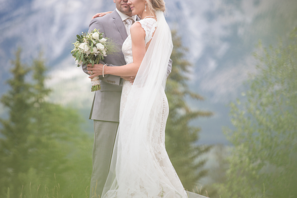 Bride & groom pose for photographs in the mountains with grey suit, white boutique, and cathedral length veil.