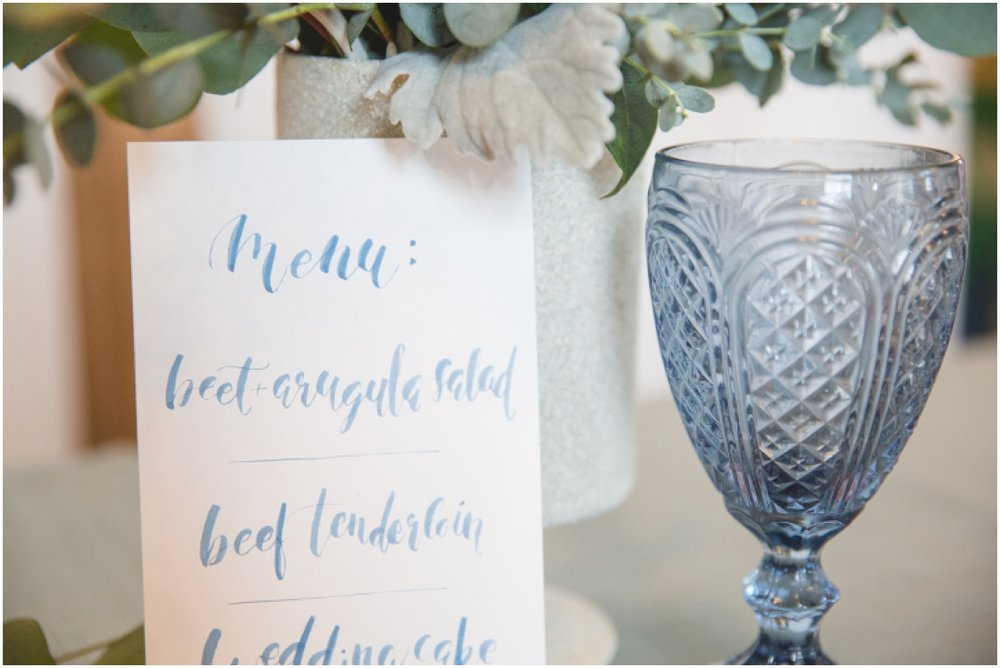 Styled wedding table with calligraphy menu, blue glassware, and eucalyptus flower arrangement