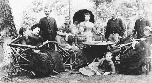 A family picnic at Forest Hill, circa 1880. Rockefeller stands at far left. Daughters Bessie, left, and Edith, right, sit directly behind the table, while Alta lounges impishly below. Cettie sits at far left and Grandmother Spelman at far right. (Courtesy of the Rockefeller Archive Center)