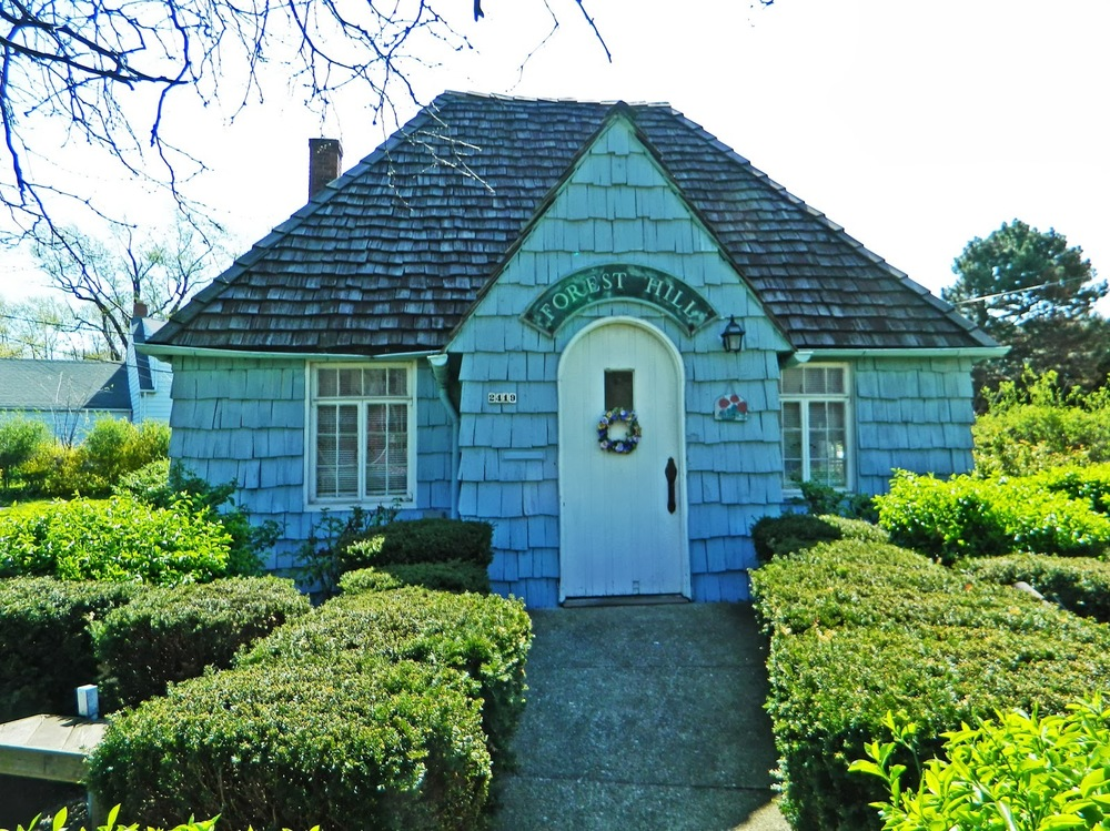 "History and Preservation of the Cottage The ""cottage"" at the southeast corner of Lee and Monticello Boulevards has served as the gateway to the Forest Hill community for three-quarters of a century.  Built in 1930 as the Forest Hill sales office of John D. Rockefeller, Jr.'s Abeyton Realty, the cottage was originally located at the corner of Brewster Road and Lee Boulevard near the ""Rockefeller homes"", where it was clearly visible driving up Lee from Euclid Avenue.  With its wavy-edged cedar shingled sides and steeply pitched cedar shake roof, the building is a miniature replica of one of Andrew J. Thomas' French Norman Rockefeller homes and acted as a unique advertisement for the development.  In 1937 the realty office was moved to its present location, closer to where homes were then being built. In 1948 Toledo businessman George A. Roose acquired the sales office when he purchased the subdivision from Rockefeller, and the cottage continued to serve as the realty office for this later phase of the Forest Hill development.  When Roose returned to Toledo, he sold the cottage, along with the original office furniture, to Forest Hill Home Owners in 1957.  FHHO continues to maintain the cottage as its office.  The cottage was designated a Cleveland Heights Landmark in 2005."