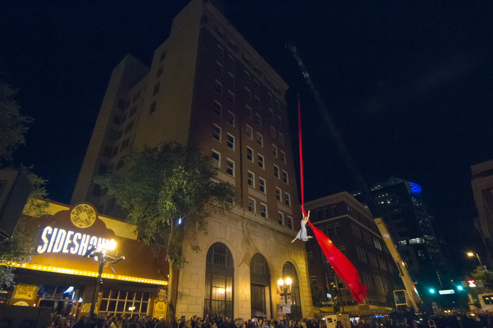 A silks performer high over a downtown street at the Creative City Project's annual event, now named, IMMERSE.