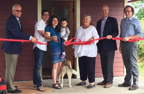 From left to right; Whatcom County Executive Jack Louws, new homeowners Joseph Hill, Megan Grosshuesch and Calvin Hill, Mayor Linville, Congressman Rick Larsen, and Executive Director of KulshanCLT, Dean Fearing, cut the ribbon on Monday, June 22, at the newly dedicated eco-friendly land trust home.