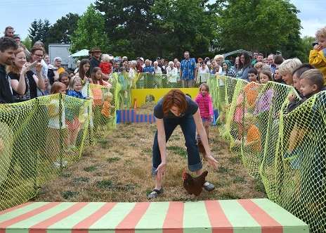 Clover Goodsir coaches her chicken Red Rocket over the final obstacle during the semi-final of the Third Annual Great Sunnyland Chicken Race on Saturday, July 11, 2015. The Great Sunnyland Chicken Race marked the beginning of the Seventh Annual Sunnyland Stomp neighborhood art walk.