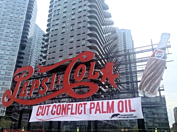 "On April 25, 2016 activists place ""cut conflict palm oil"" banner under the PepsiCola sign in New York City to protest worker exploitation, human rights abuses and deforestation (Photo by RAN)."