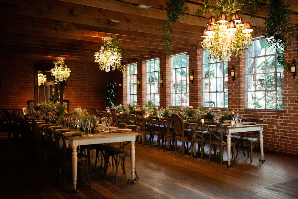 Rustic dinner party with long farm tables and chandeliers designed by Eddie Zaratsian for the Allison Webb Spring 2019 Bridal Collection, Photo by Jessica Grazia Mangia Photography