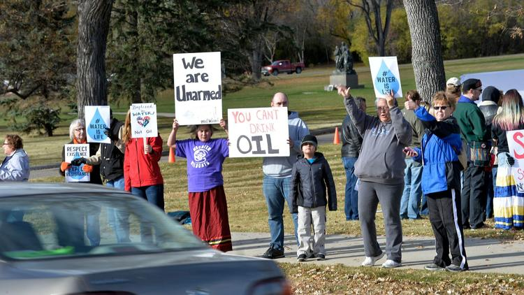 Pipeline protesters hold signs for passing motorists during a rally on the south side of the state Capitol in Bismarck, N.D., on Saturday. (Will Kincaid / The Bismarck Tribune) via LA Times