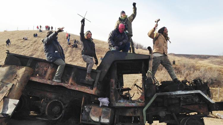 Protesters against the Dakota Access oil pipeline stand on a burned-out truck near Cannon Ball, N.D., on Nov. 21. (James MacPherson / Associated Press) via LA Times