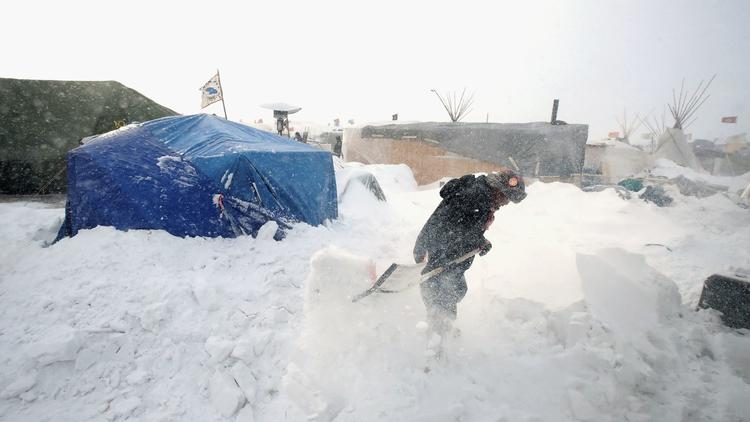 Efrem John, a Dine Navajo from Shiprock, N.M., clears snow from his camp near the Standing Rock Sioux Reservation in North Dakota. (Scott Olson / Getty Images via LA Times)