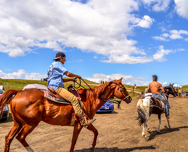 Two Standing Rock demonstrators take to horseback as part of the Standing Rock demonstrations that peaked in 2016. (Photo: Robert Wilson, via PRI)