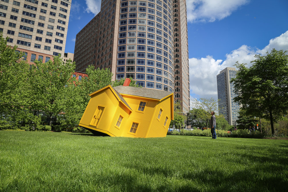 Yellow house that sinks into the grass