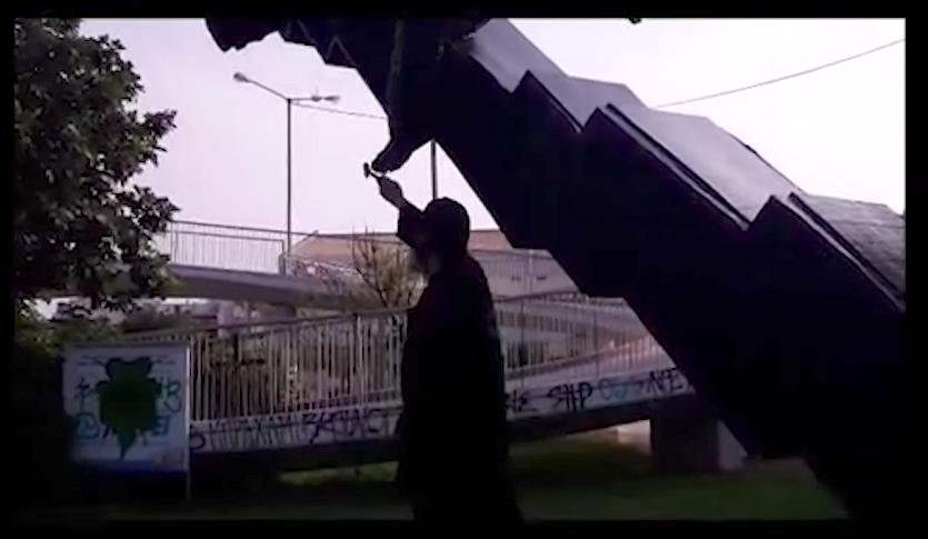 "YouTube still of ""Priest Kleomenis"" damaging the artwork with a hammer"