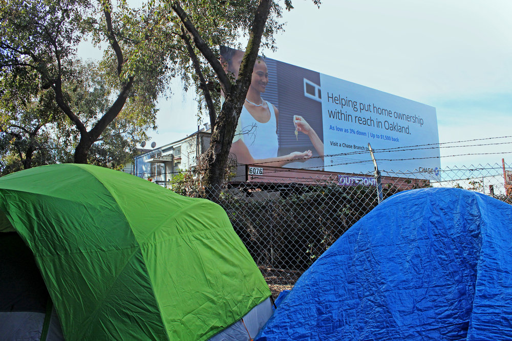 "The Northgate encampment stands in the shadow of a Chase Bank billboard advertisement. The ""A House in Oakland"" team has left this billboard untouched."
