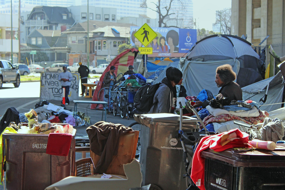 "The Northgate encampment is located on Northgate Ave under the I-980 freeway. A sign in the background reads, ""Homeless lives matter too."""