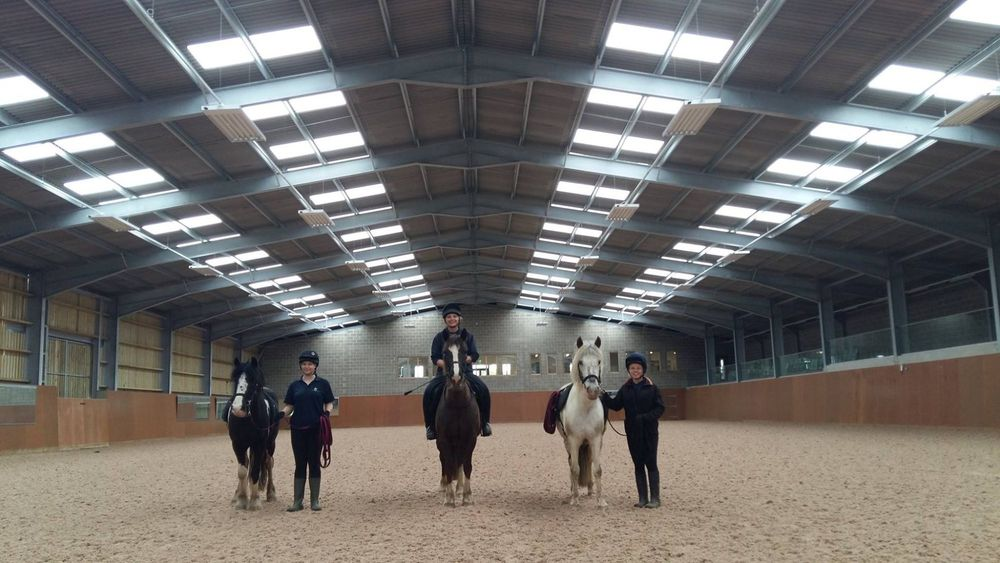 Grooms and horses enjoying the indoor arena at Glenda Spooner Farm