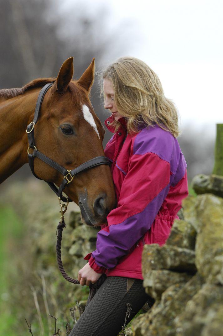 lady cuddling horse